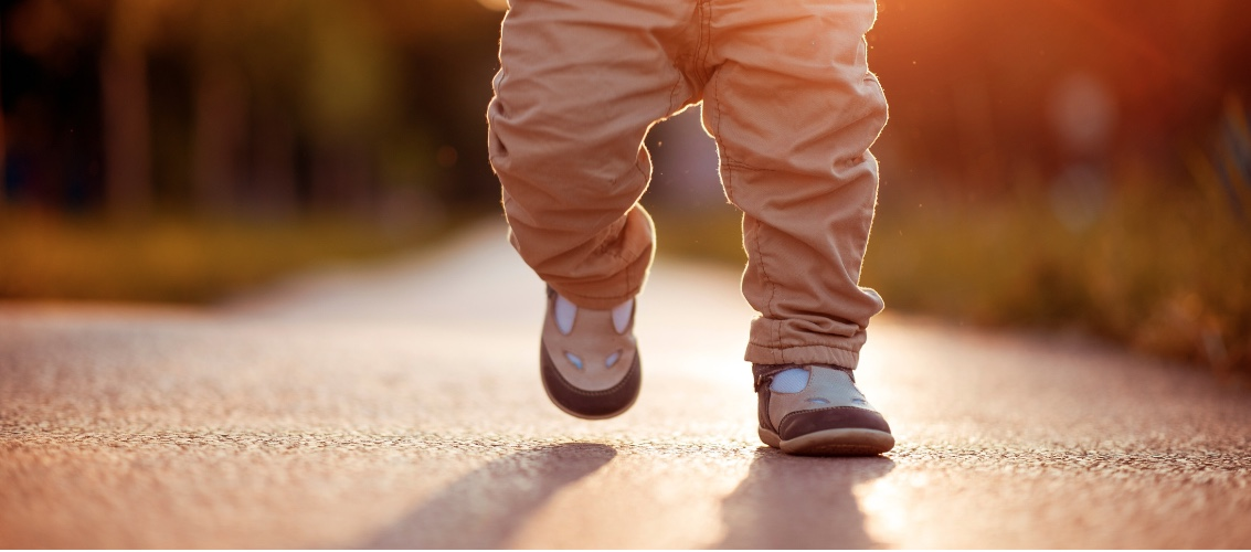image of toddler's feet running on pavement in sunset